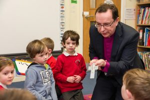 Bishop Philip Mounstephen shows his pectoral cross to a group of children from Ladock School